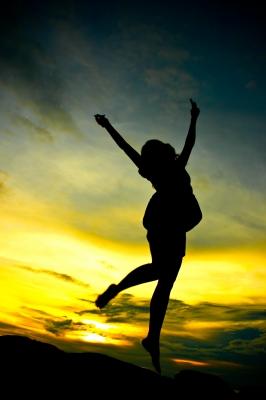 bonheur femme qui saute sur un couché de soleil